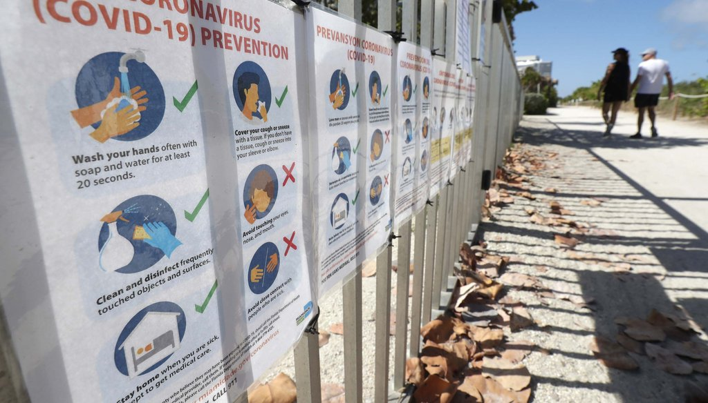 Coronavirus prevention flyers attached to a fence of the town's community center are shown on March 21, 2020, in Surfside, Fla. (AP)