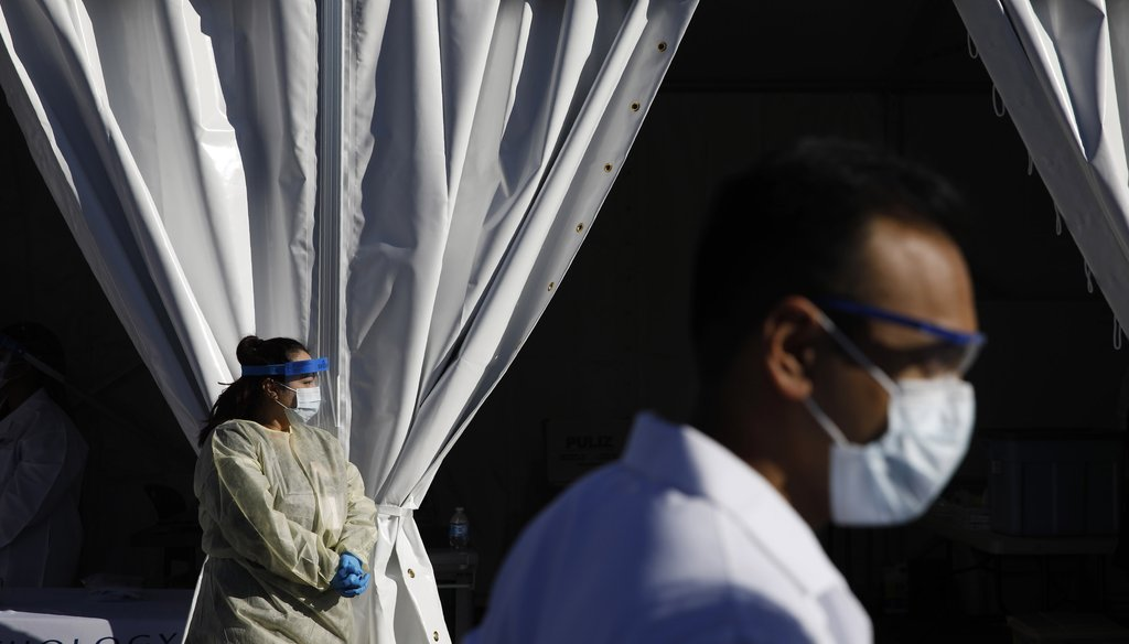 Health care workers with the UNLV School of Medicine wait in personal protective equipment for patients at a drive thru coronavirus testing site on March 24, 2020, in Las Vegas. (AP)