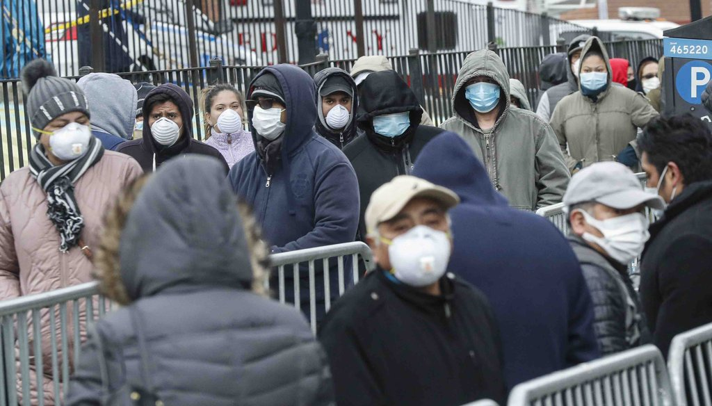 Patients wear personal protective equipment while maintaining social distancing as they wait in line for a COVID-19 test at Elmhurst Hospital Center on March 25, 2020, in New York. (AP)