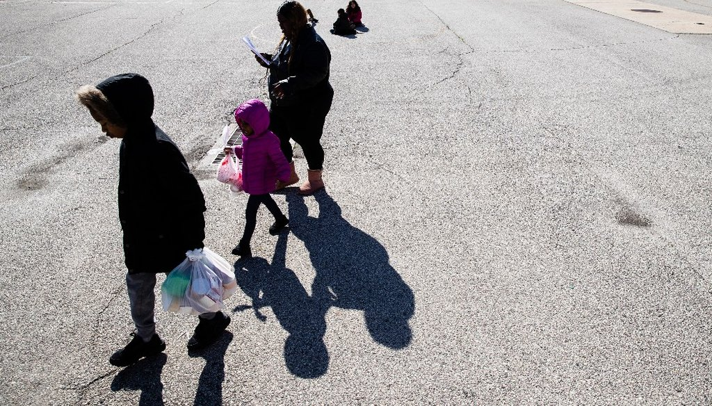 A woman and children walk away from the John H. Webster Elementary School carrying donated food and educational materials, in Philadelphia, Thursday, March 26, 2020. (AP)