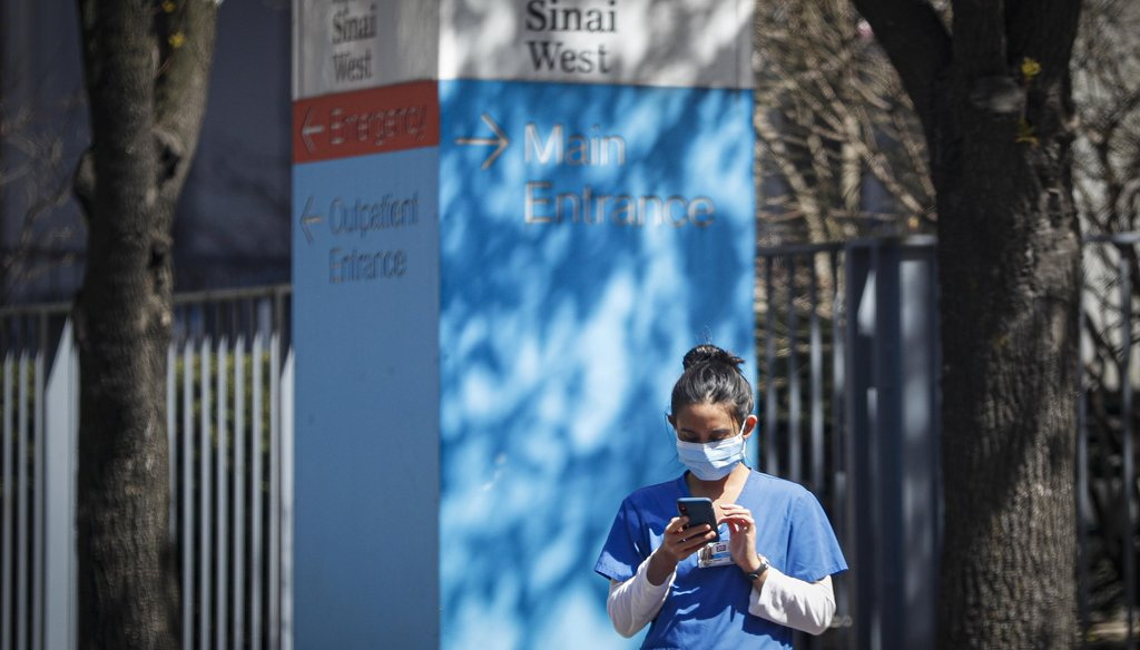 A medical worker uses her phone while wearing a surgical mask outside Mt. Sinai West on March 26, 2020, in New York. (AP)