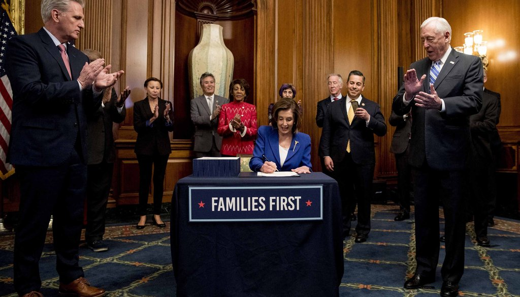 House Speaker Nancy Pelosi of California signs the Coronavirus Aid, Relief, and Economic Security (CARES) Act after it passed in the House on Capitol Hill on March 27, 2020, in Washington. (AP)