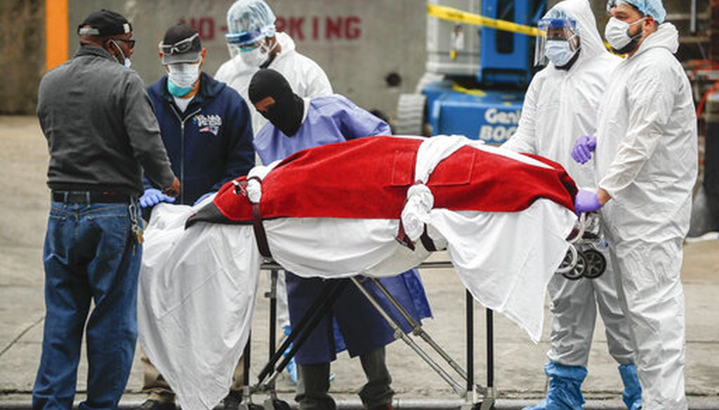 A body wrapped in plastic that was unloaded from a refrigerated truck is handled by medical workers wearing personal protective equipment on March 31, 2020, at Brooklyn Hospital Center in New York City. (AP)