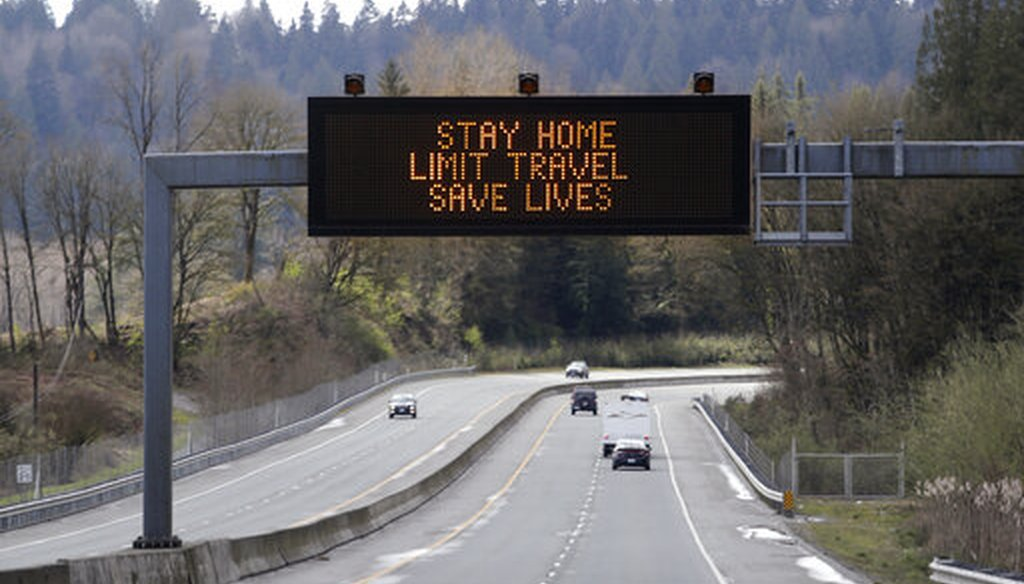 """A sign overhead on an unusually quiet highway reminds drivers to """"Stay home, limit travel, save lives"""" as part of Washington Gov. Jay Inslee's ongoing stay-at-home order in the midst of the coronavirus, April 1, 2020, in Monroe, Wash. (AP/Elaine Thompson)"""