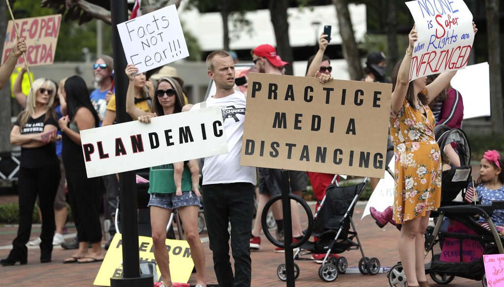Protesters demanding Florida businesses and government reopen, march in downtown Orlando, Fla., on April 17, 2020. (AP)