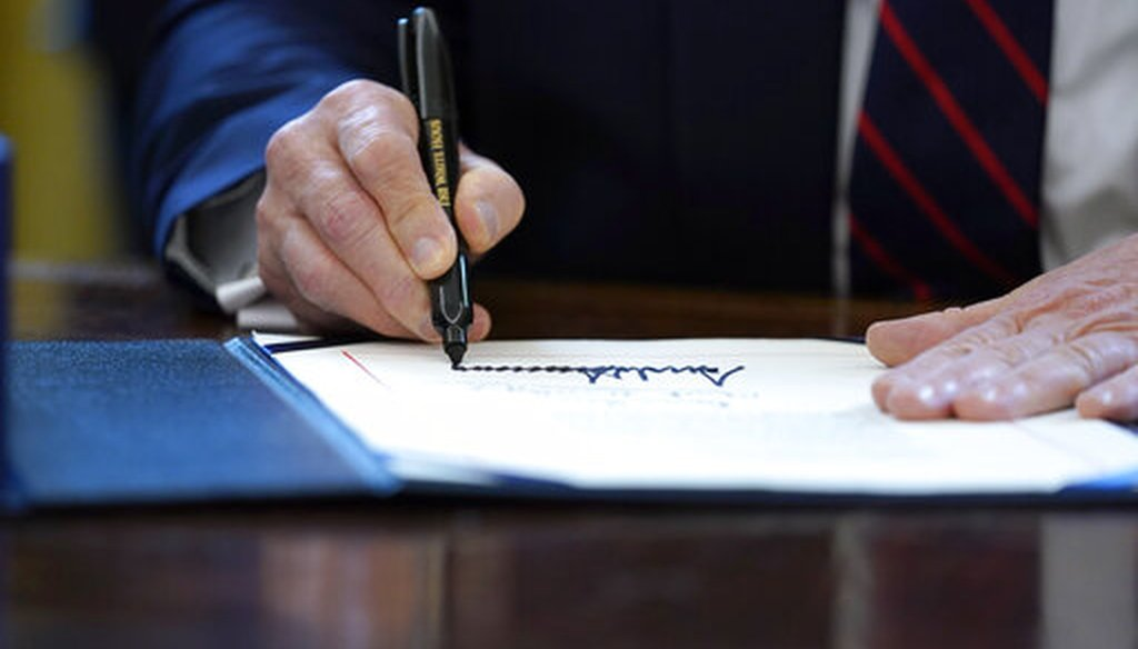 In this March 27, 2020 file photo, President Donald Trump signs the coronavirus stimulus relief package in the Oval Office at the White House in Washington. (AP/Evan Vucci)