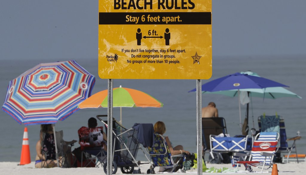 Beachgoers sunbathe near a beach rules sign after Clearwater Beach officially reopened to the public Monday, May 4, 2020. (AP)