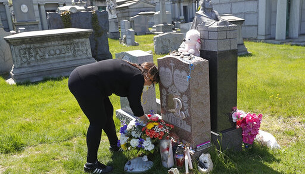 Sharon Rivera adjusts flowers left on her daughter's grave at Calvary Cemetery on Mother's Day, May 10, 2020, in New York. Rivera's daughter Victoria died at 21 of a drug overdose on Sept. 22, 2019. (AP)