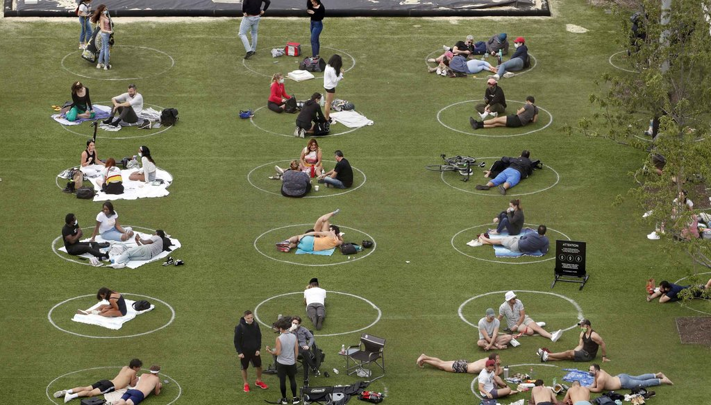 People relax in marked circles for proper social distancing at Domino Park in the Williamsburg neighborhood of Brooklyn during the current coronavirus outbreak on May 17, 2020, in New York. (AP)