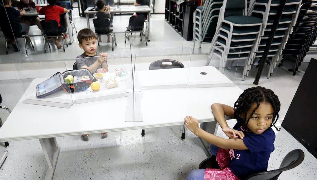 Plastic barriers are placed between children as they sit at a table during martial arts daycare summer camp at Legendary Blackbelt Academy in Richardson, Texas on May 19, 2020. (Associated Press)