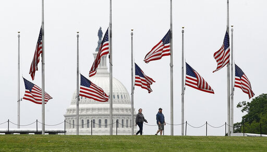 On May 22, 2020, walkers pass American flags flying at half-staff at the Washington Monument in Washington. (AP/Semansky)