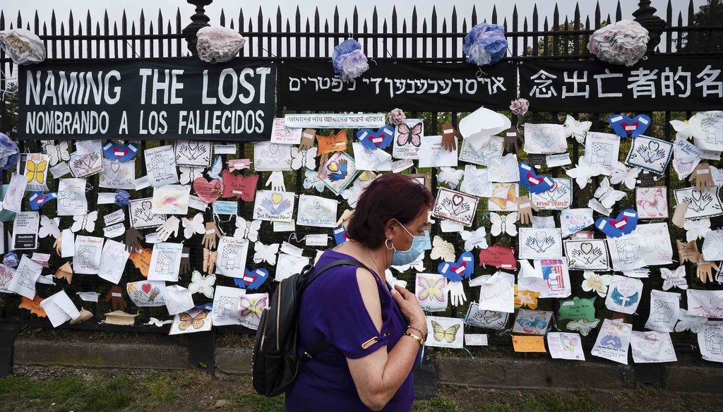 A woman passes a fence outside Brooklyn's Green-Wood Cemetery adorned with tributes to victims of COVID-19 on May 28, 2020, in New York. (AP)