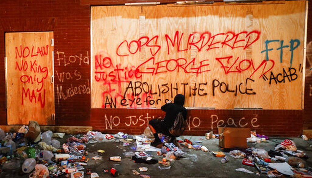 A protester sprays graffiti on a wall near the Minneapolis 3rd Police Precinct on May 28, 2020, in Minneapolis. (AP/Minchillo)