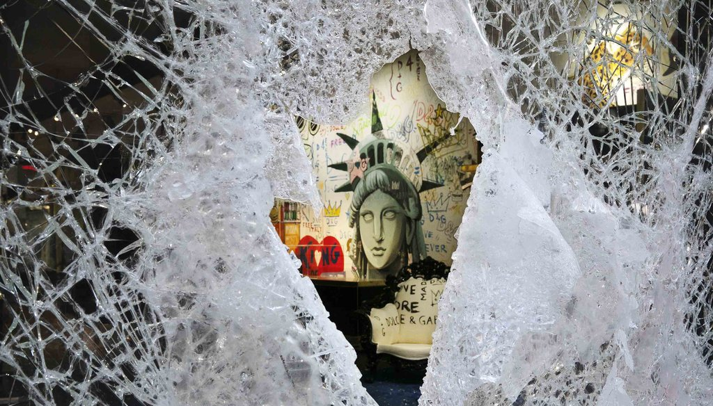 A Statue of Liberty painting is seen through a smashed Dolce and Gabbana store window on June 1, 2020, in the SoHo neighborhood of New York. (AP)