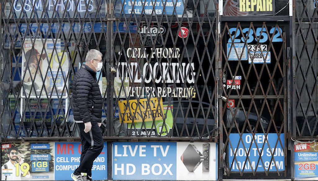In a April 30, 2020 file photo, a man walks by a closed store during the COVID-19 in Chicago. (Associated Press)