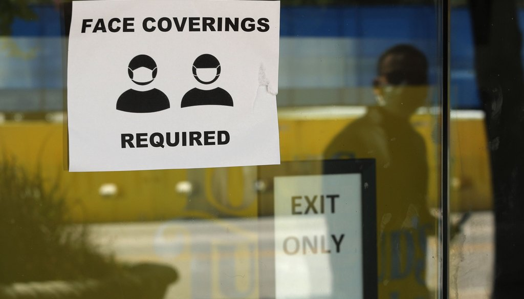 A man wearing mask to protect against the spread of COVID-19 is reflected next to a sign requiring face coverings at a business in San Antonio on June 24, 2020. (AP)