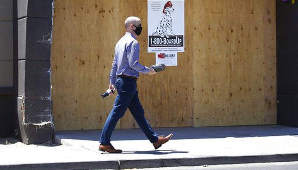 A pedestrian with a takeout lunch in hand walks through an area of Scottsdale, Ariz., known for busy restaurants, bars and nightlife, June 30, 2020. (AP/Ross D. Franklin)
