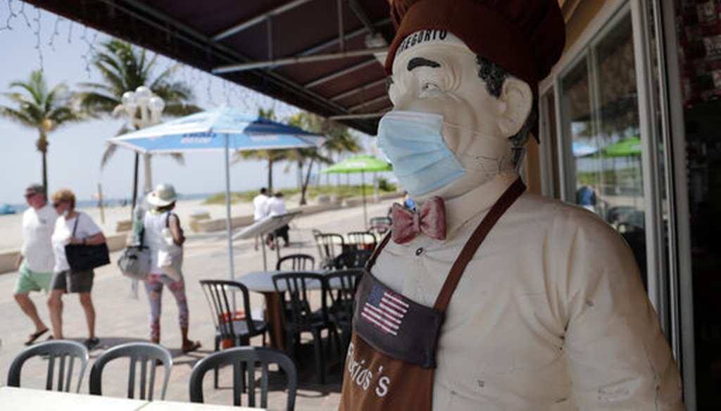 A statue of a chef at Florio's of Little Italy restaurant wears a protective face mask on the Hollywood Beach Broadwalk during the new coronavirus pandemic, Thursday, July 2, 2020, in Hollywood, Fla. (AP Photo)