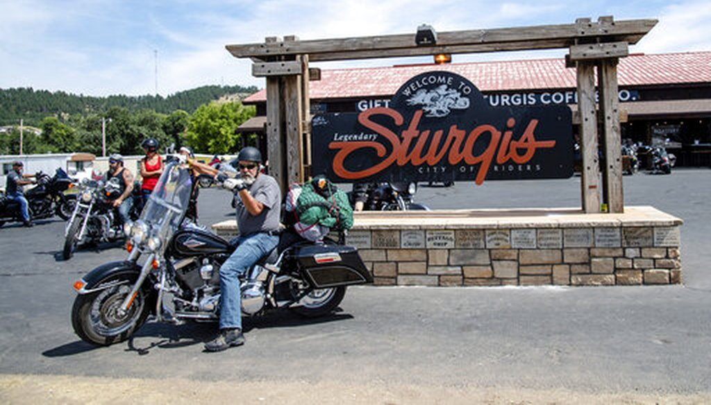 A biker poses in front of the Sturgis welcome sign during the 80th annual Sturgis Motorcycle Rally on Aug. 15, 2020, in Sturgis, S.D. (AP/Harris)