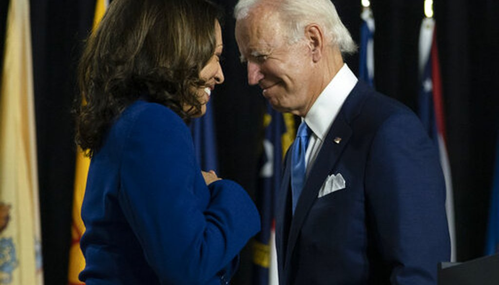 Democratic presidential candidate Joe Biden and his running mate, Sen. Kamala Harris, D-Calif., pass each other as Harris moves to the podium to speak during a campaign event in Delaware, Aug. 12, 2020 (AP)