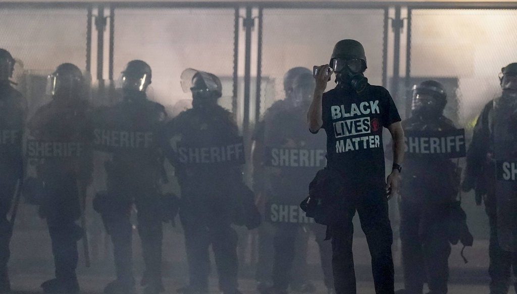A protester holds up a phone as he stands in front of authorities on Aug. 25, 2020, in Kenosha, Wis. (AP)