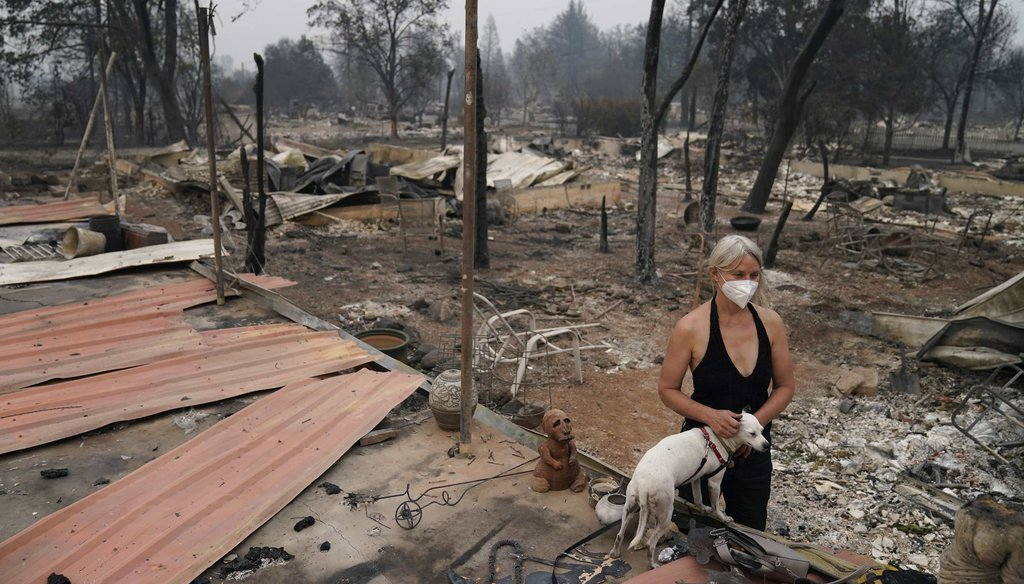 Eden McCarthy pets her dog Hina in the rubble of her home destroyed by the Almeda Fire on Sept. 10, 2020, in Talent, Ore. (AP)