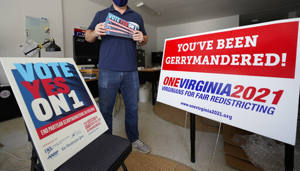 Redistricting reform advocate Brian Cannon poses with some of his yard signs on Oct. 6, 2020, in Richmond, Va. (AP)
