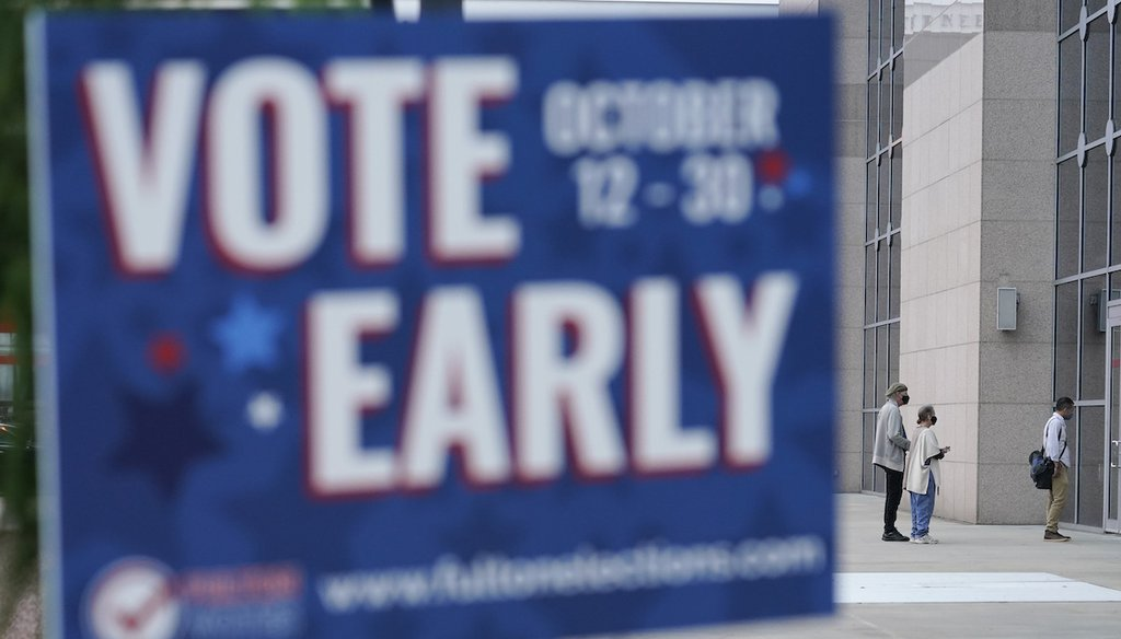 Behind a sign listing early voting dates for Fulton County, Georgia, a line forms outside of the State Farm Arena for early voting on Oct. 12, 2020, in Atlanta. (AP/Anderson)