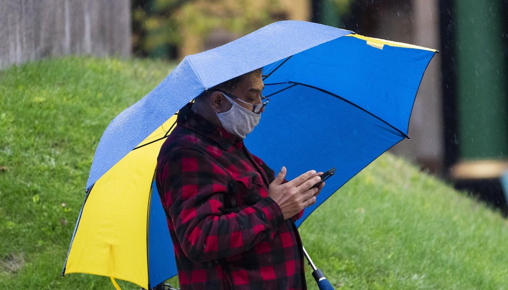 A man wears a mask to help prevent the spread of the coronavirus while using his phone on a rainy day. (AP)
