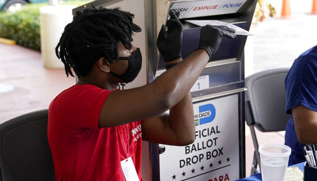 Election worker Najeh Fisher places a vote-by-mail ballot for the Nov. 3 general election into an official ballot drop box at the Miami-Dade County Elections Department, Wednesday, Oct. 14, 2020, in Doral, Fla. (AP)