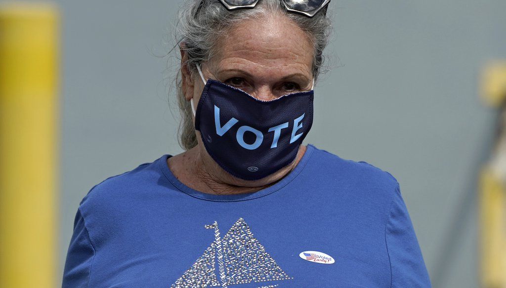 """Sylvia Faria, of Lakeland, Fla., wears a """"vote"""" mask as she leaves after early voting at the Polk County Government Center Monday, Oct. 19, 2020, in Lakeland, Fla.  (AP)"""