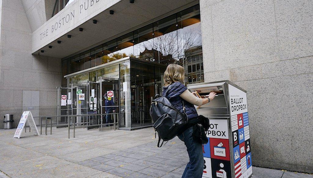 Voter Linda Borman drops her ballot into the ballot box outside the Boston Public Library, Monday, Oct. 26, 2020, in Boston. (AP)