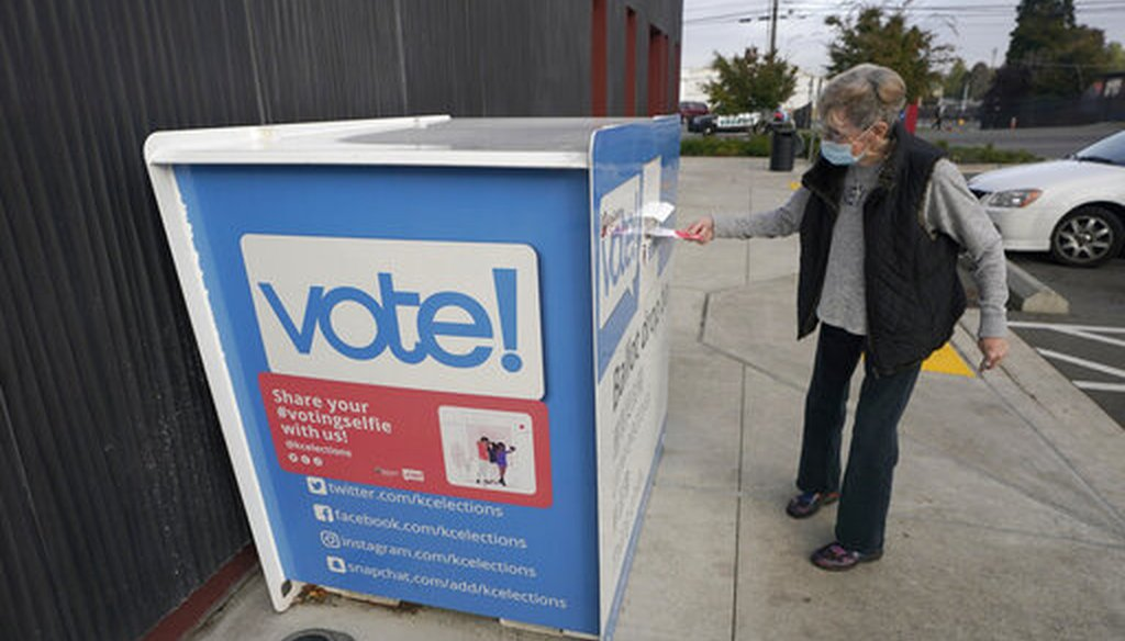 A woman puts a ballot in a drop box on Oct. 27, 2020, at a library in Seattle. (AP)