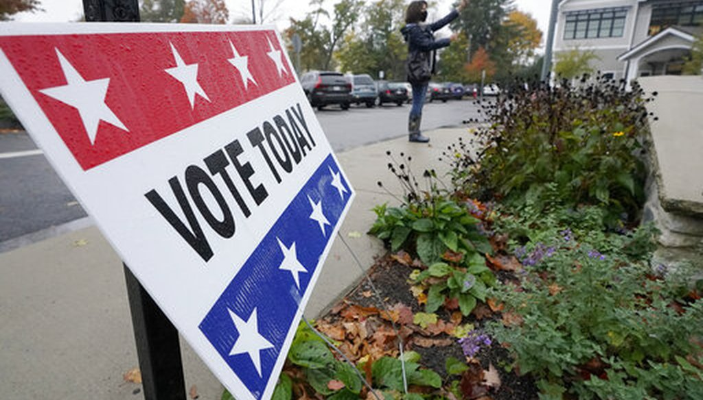A passers-by uses a mobile device near a vote today sign outside a polling place during early in-person general election voting, Oct. 28, 2020, Wellesley, Mass. (AP)