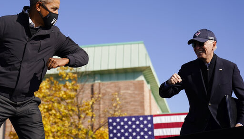 Democratic presidential candidate Joe Biden, right, and former President Barack Obama greet each other with an air elbow bump, at a rally in Flint, Mich., Oct. 31, 2020. (AP)