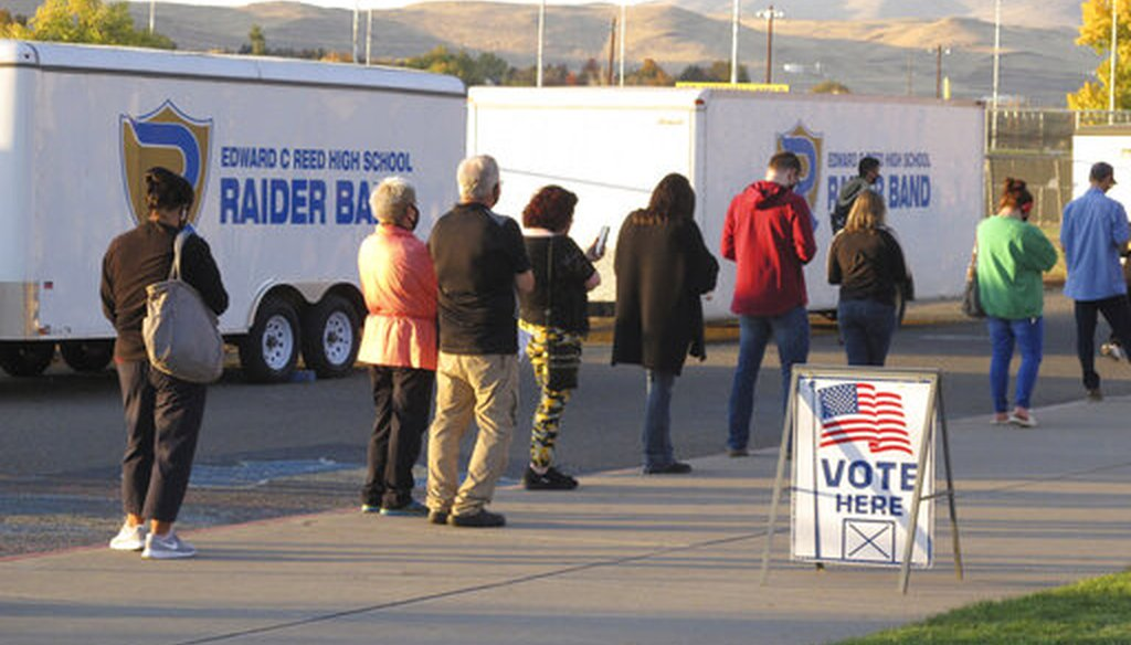 About 100 mostly masked northern Nevadans were waiting to vote in person at Reed High School in Sparks along the eastern front of the Sierra about two hours before the polls closed, Nov. 3, 2020. (AP)