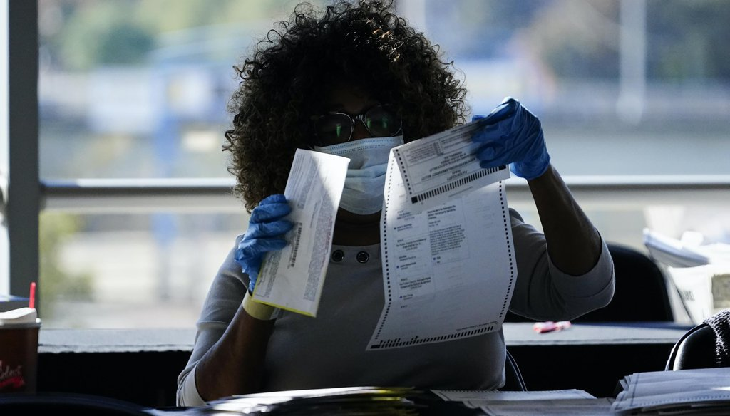 An election personnel examines a ballot as vote counting in the general election continues at State Farm Arena on Nov. 4, 2020, in Atlanta. (AP)