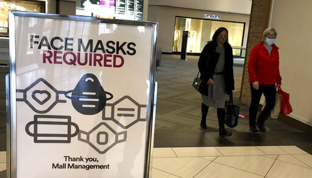 "In this Nov. 13, 2020 file photo, a ""Face masks required"" sign is displayed at a shopping center in Schaumburg, Ill. (AP)"