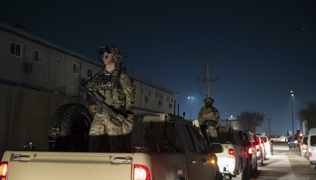 Armed soldiers stand guard in the motorcade for President Donald Trump during his surprise Thanksgiving Day visit at Bagram Air Field, Afghanistan, Nov. 28, 2019(AP)