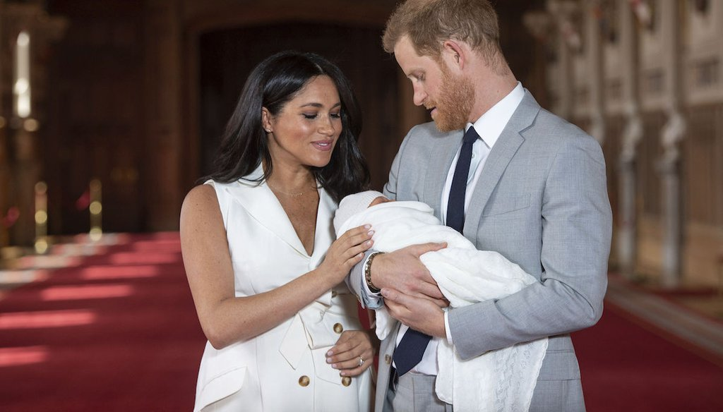 Prince Harry and Meghan, Duchess of Sussex, pose with their son Archie in St George's Hall at Windsor Castle in Windsor, south England, on May 8, 2019. (AP/Lipinski)