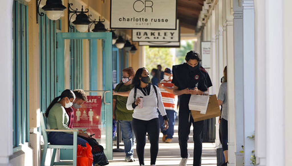 Shoppers wear protective face masks as they look for Black Friday deals at the Ellenton Premium Outlet stores on Nov. 27, 2020, in Ellenton, Fla. (AP)