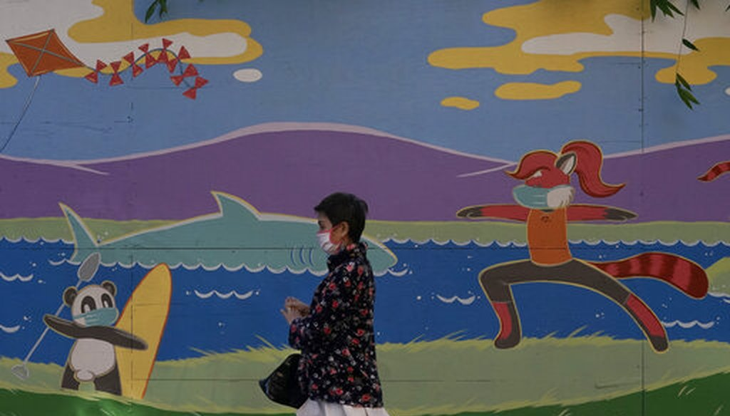 A pedestrian wears a mask while walking in front of a mural during the coronavirus pandemic in San Jose, Calif., Dec. 1, 2020. (AP)