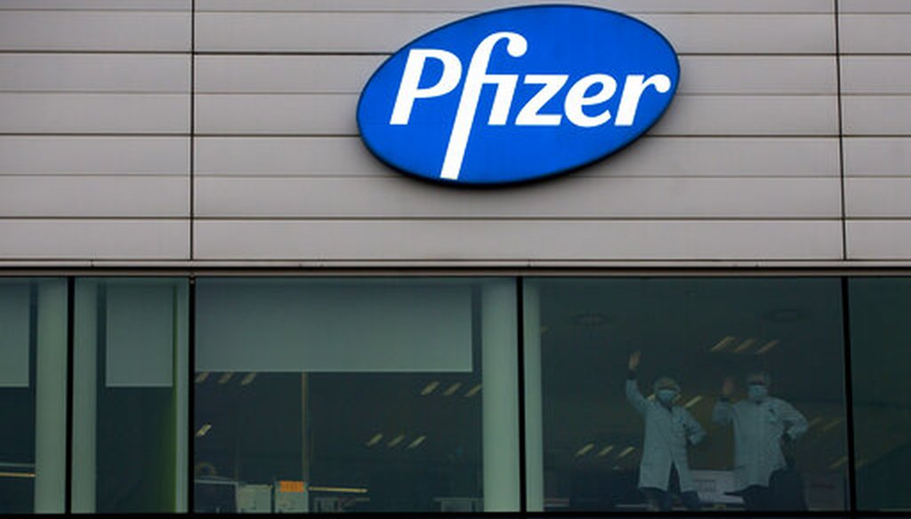 Two workers wave from a window at Pfizer Manufacturing in Puurs, Belgium, on Dec. 2, 2020. (AP/Mayo)