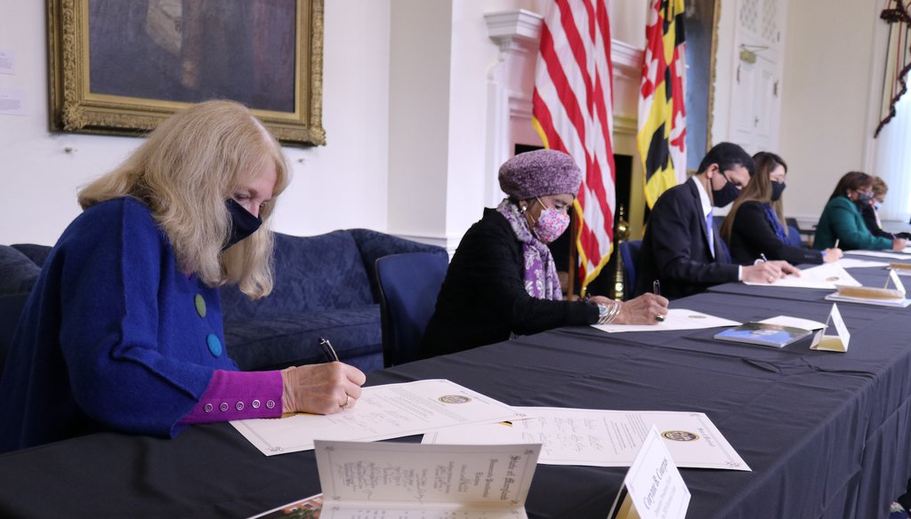 Corynne Courpas, left, signs a certificate during the formal vote of Maryland's 10 electors for Democrat Joe Biden for president and Kamala Harris for vice president. (AP)