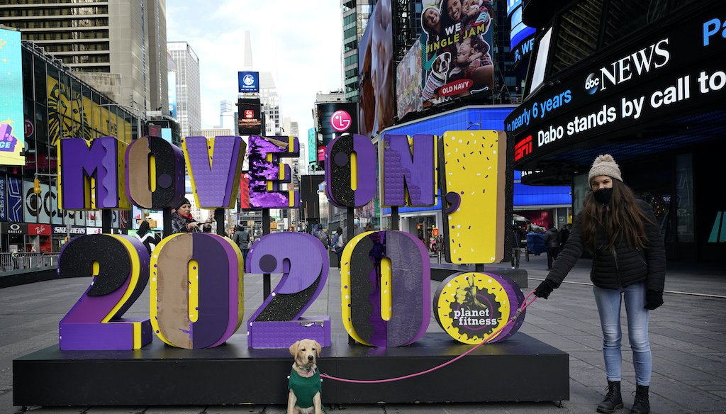 "Simona Faidiga makes sure Maggie, her dog, stays in position for a picture in front of a sign that reads ""Move On 2020!"" In Times Square, New York, Monday, Dec. 28, 2020. (AP)"