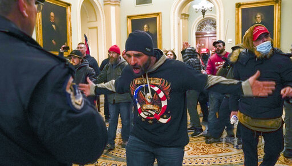 Trump supporters gesture to U.S. Capitol Police in the hallway outside of the Senate chamber on Jan. 6, 2021. (AP/Manuel Balce Ceneta)