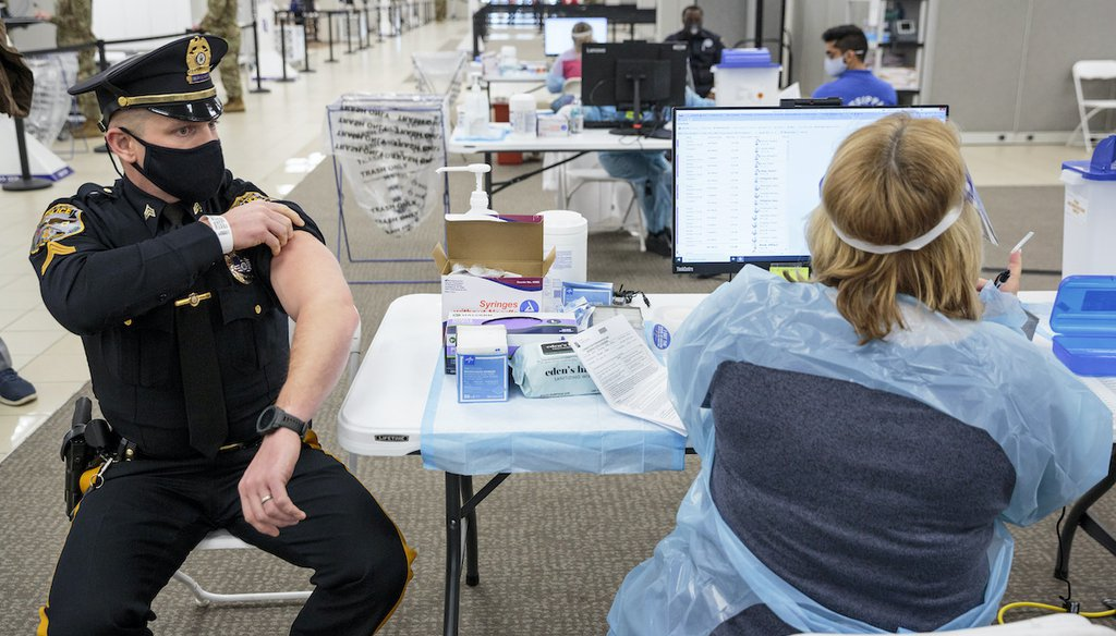 Sergeant Michael Zarro, of the Mount Olive, NJ, Police Department, rolls up his sleeve to receive a COVID-19 vaccination at the Morris County, vaccination site, in Rockaway, NJ, Jan. 8, 2021. (AP)