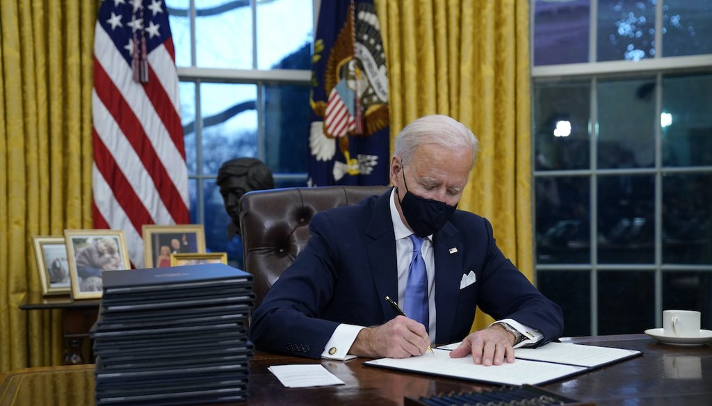 President Joe Biden signs his first executive order in the Oval Office of the White House on Jan. 20, 2021, in Washington. (AP)