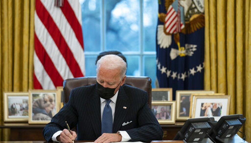 President Joe Biden signs an executive order in the Oval Office on Jan. 25, 2021,. (AP)