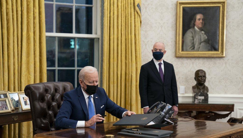 Secretary of Homeland Security Alejandro Mayorkas looks on as President Joe Biden puts away a signed executive order on immigration, Feb. 2, 2021. (AP)